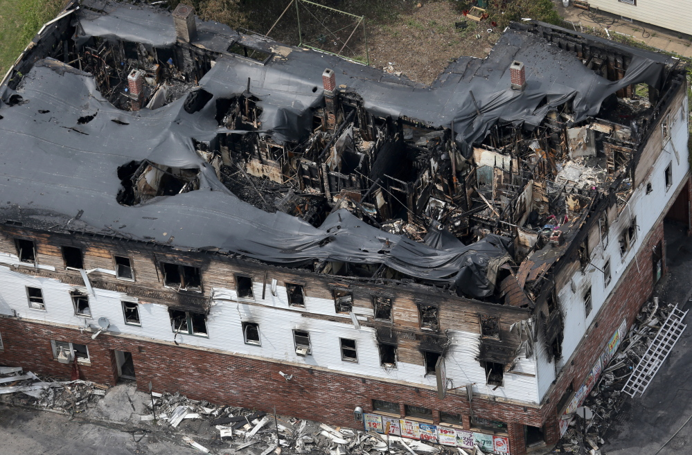 Fire engulfed the top floors of a three-story apartment and business building early Thursday in Lowell, Mass. Officials confirmed that seven people including three children died in the fire on Branch Street.