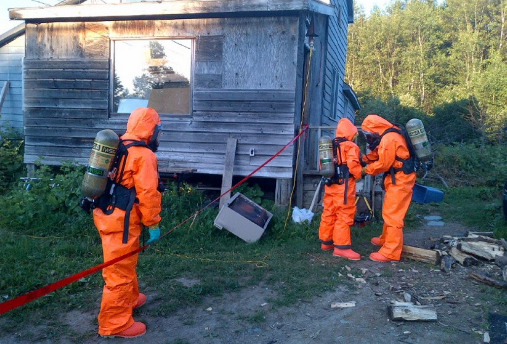A Maine Drug Enforcement Agency team wears protective gear to dismantle a suspected methamphetamine lab in the Aroostook County town of Merrill on Wednesday.