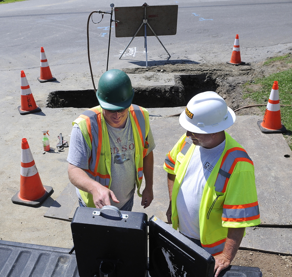 McGee Construction employees Tom Towns, left, and Ted Haskell record the pressure of a natural gas pipeline on Tuesday at the intersection of Maple and Greenville streets in Hallowell.