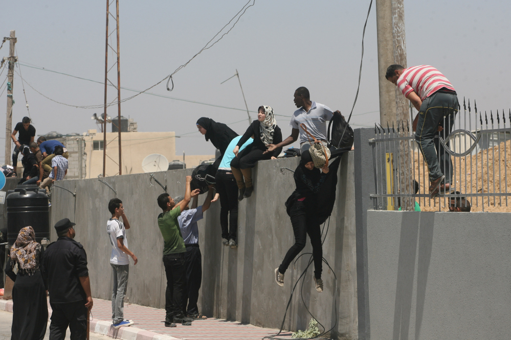 Palestinians climb a wall over as they try to cross into Egypt at the border between the Gaza Strip and Egypt in Rafah on Thursday. Egyptian authorities opened the border to let wounded Palestinians cross for medical treatment in Egyptian hospitals.