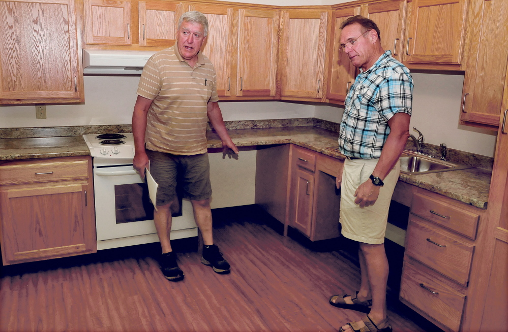 Byron Davis, left, and Bill Marceau, show one of the apartments in their newly opened Brookside Village senior residence in Farmington on Tuesday. Davis is explaining how counters are lower and allow access underneath for residents in wheelchairs.