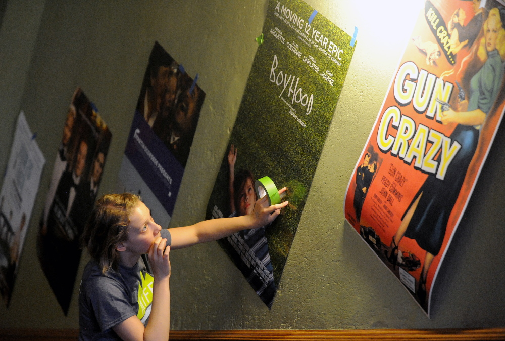 Bria Watson, MIFF venue manager, hangs posters in the lobby of the Waterville Opera House in Waterville on Thursday. The Maine International Film Festival kicks off this weekend.