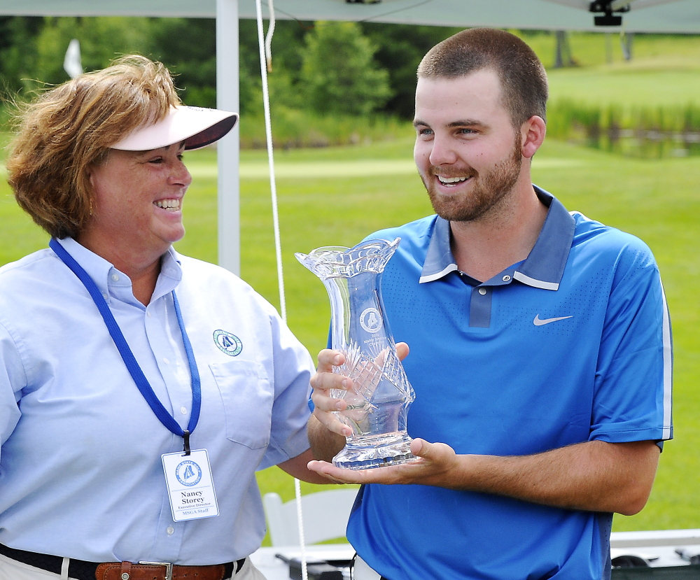 Maine State Golf Association Director Nancy Storey, left, hands the trophy to Andrew Slattery after the final round of the Maine Amateur Championship on Thursday at the Woodlands in Falmouth. Slattery won by one stroke.