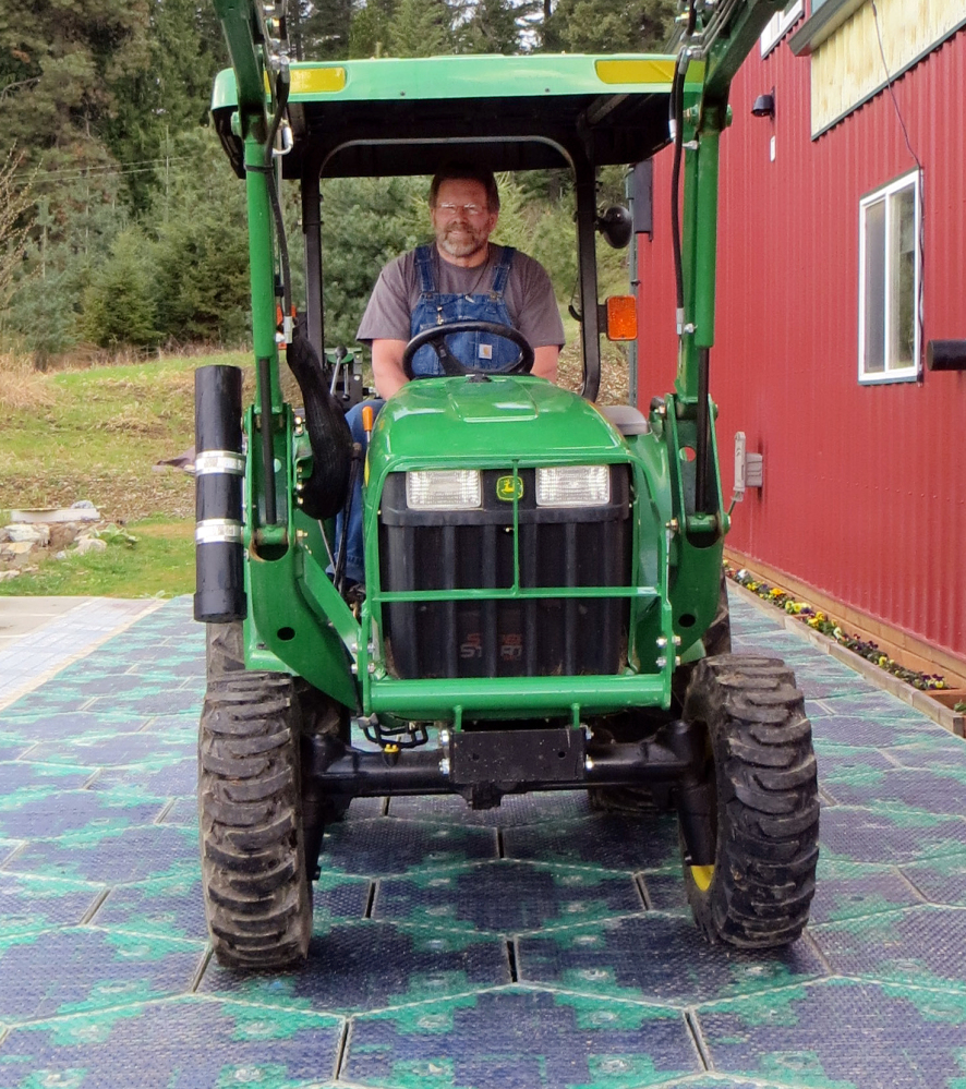 Scott Brusaw drives a tractor on a prototype solar-panel parking area at his company's headquarters in Sandpoint, Idaho. Skeptics wonder about the durability of the panels, which are covered by knobby, tempered glass.