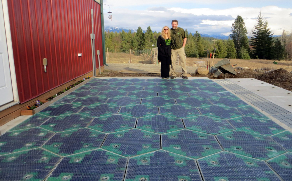 Scott and Julie Brusaw stand on a prototype solar-panel parking area at their company's headquarters in Sandpoint, Idaho, in this photo provided by Solar Roadways.