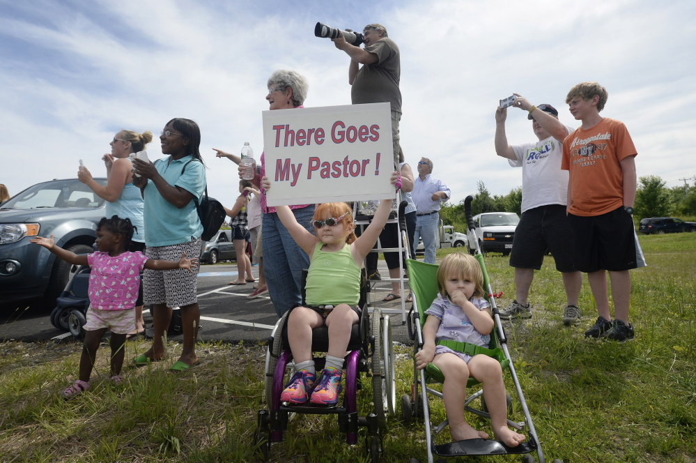 Four-year-old Sophia Emerson of Biddeford, accompanied by her 1-year-old sister Natalie, cheers   Members of The Rock Church in Scarborough cheer their pastor, Lt. Col. Eric Samuelson, as he made a final flight in the high-performance F-15, buzzing the Portland Jetport Thursday, July 10, 2014. Holding the sign in support of her pastor is Sophia Emerson 4, of Biddeford and to the right her younger sister Natalie Emerson, 1, of Biddeford. (Photo by Shawn Patrick Ouellette/Staff Photographer).