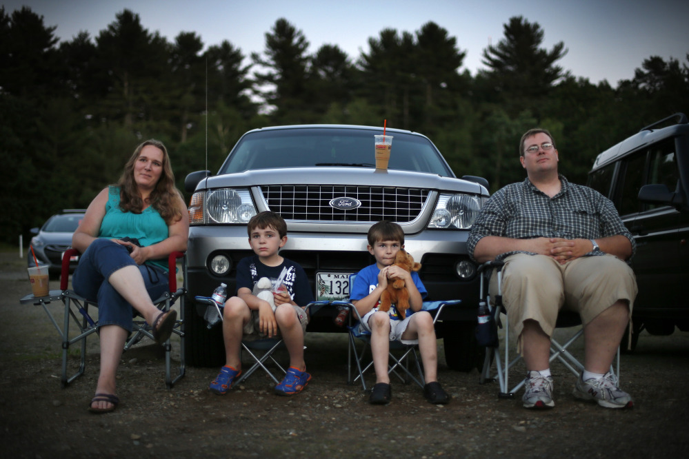 Jen and Philip Mason, along with their sons Skyelar, left, and Trysten, watch the previews at the Saco Drive-In in Saco. Many in the movie industry feared the need to convert to digital could be the death knell for drive-ins, but drive-in operators are finding creative ways to afford the switch.