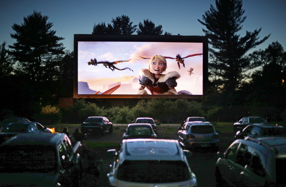 Movie-goers watch How to Train Your Dragon 2, the first movie of a double feature at the Saco Drive-In in Saco. Drive-in movie theater operators say more than 200 of the remaining 348 drive-ins in the country have made the costly switch from film to digital.