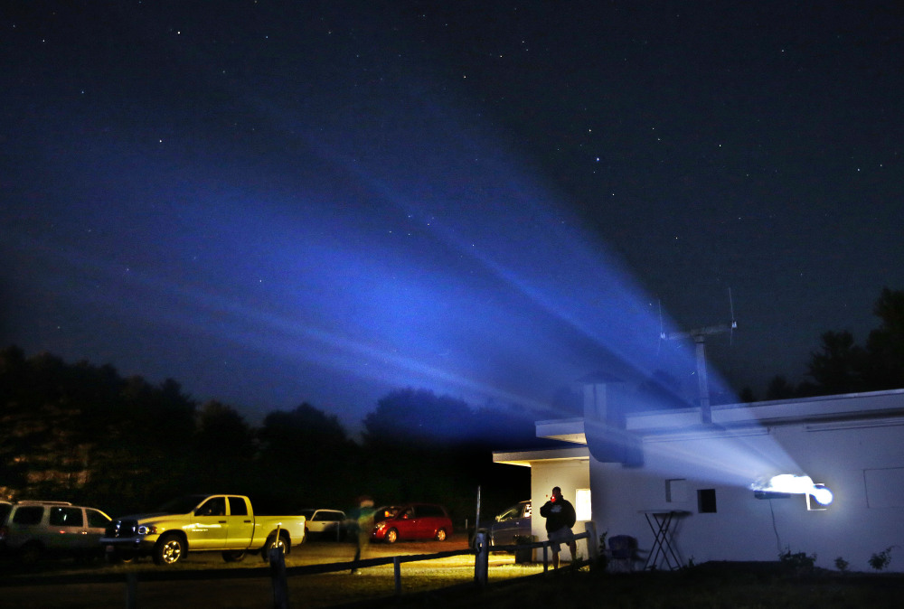 Light from a digital projector beams from the projection house at the Saco Drive-In in Saco.