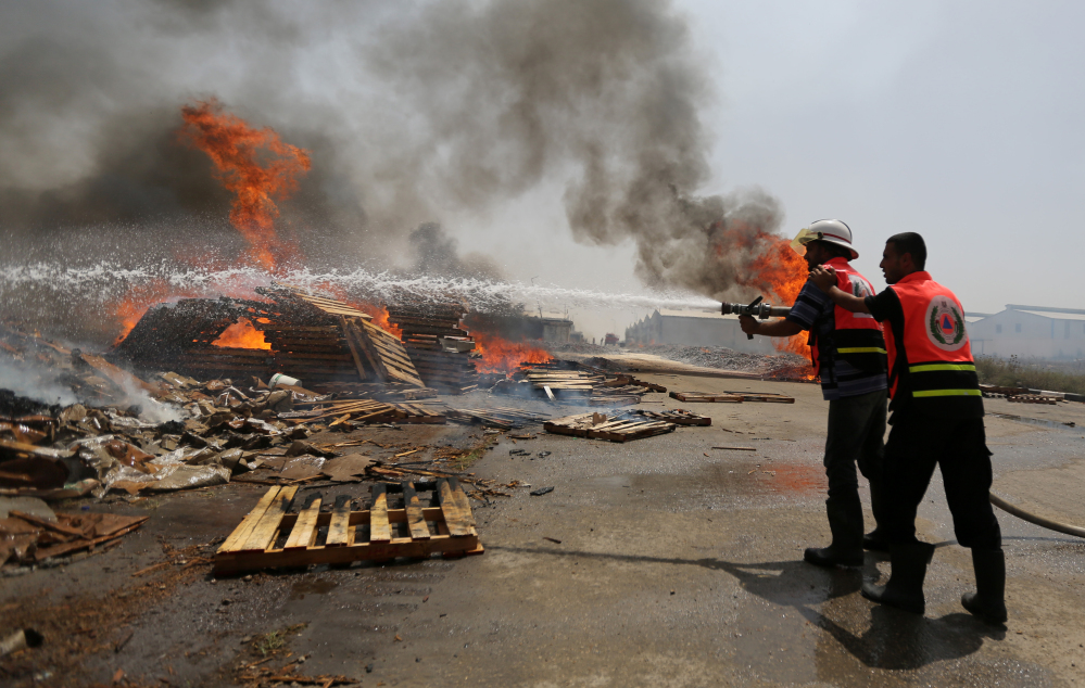 Palestinian firefighters try to extinguish a cargo terminal at Karni Crossing between Israel and Gaza  after it was shelled by Israeli tanks, according to terminal's employees, on Saturday.
