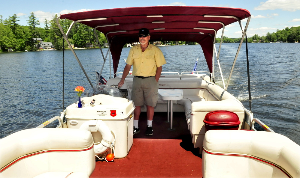 Gary Bennett, owner of Snow Pond Cruises, pilots his Snowdrifter ll boat on Thursday. The boat can carry up to 19 passengers for leisurely trips on Messalonskee Lake.