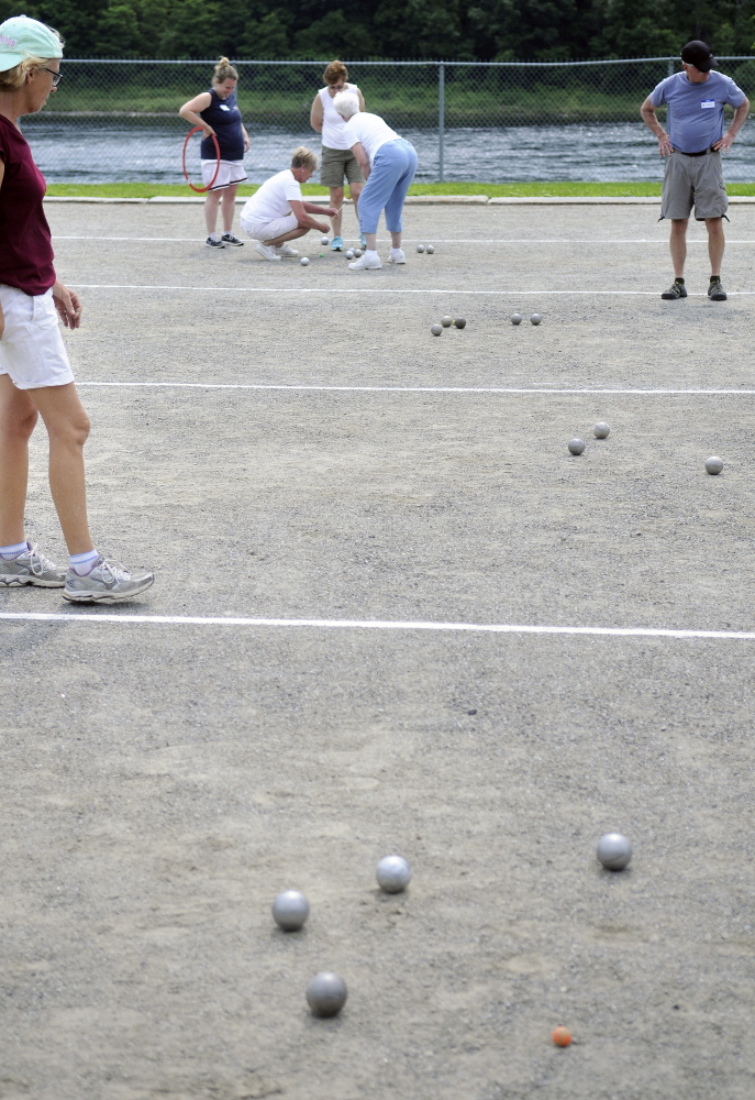 Petanque players assess their balls Sunday during a tournament at Mill Park in Augusta.