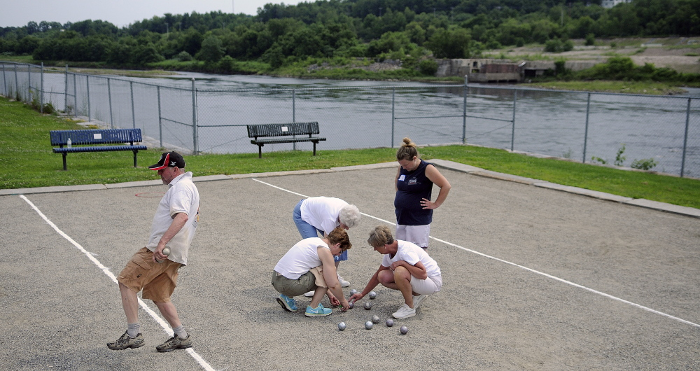 Mark Kindschi reacts Sunday to a bowl during the petanque tournament at Mill Park in Augusta as another team counts points at the court beside the Kennebec River.