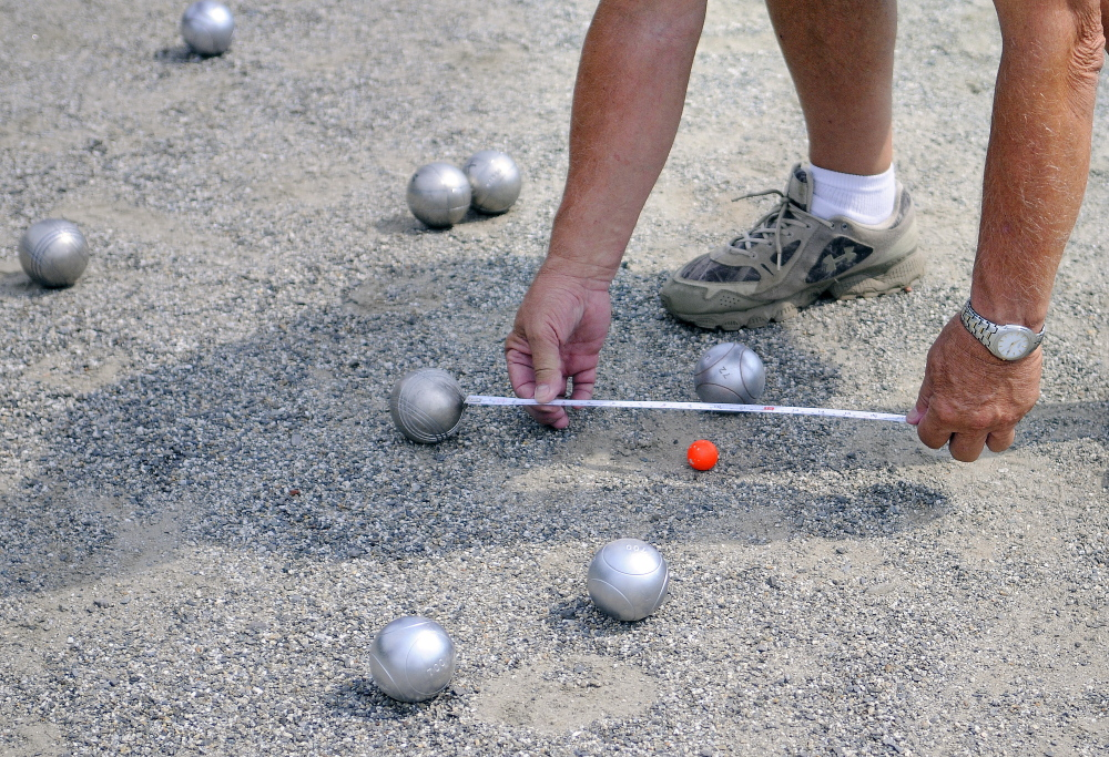A judge measures the distance Sunday between petanque balls during a tournament at Mill Park in Augusta.