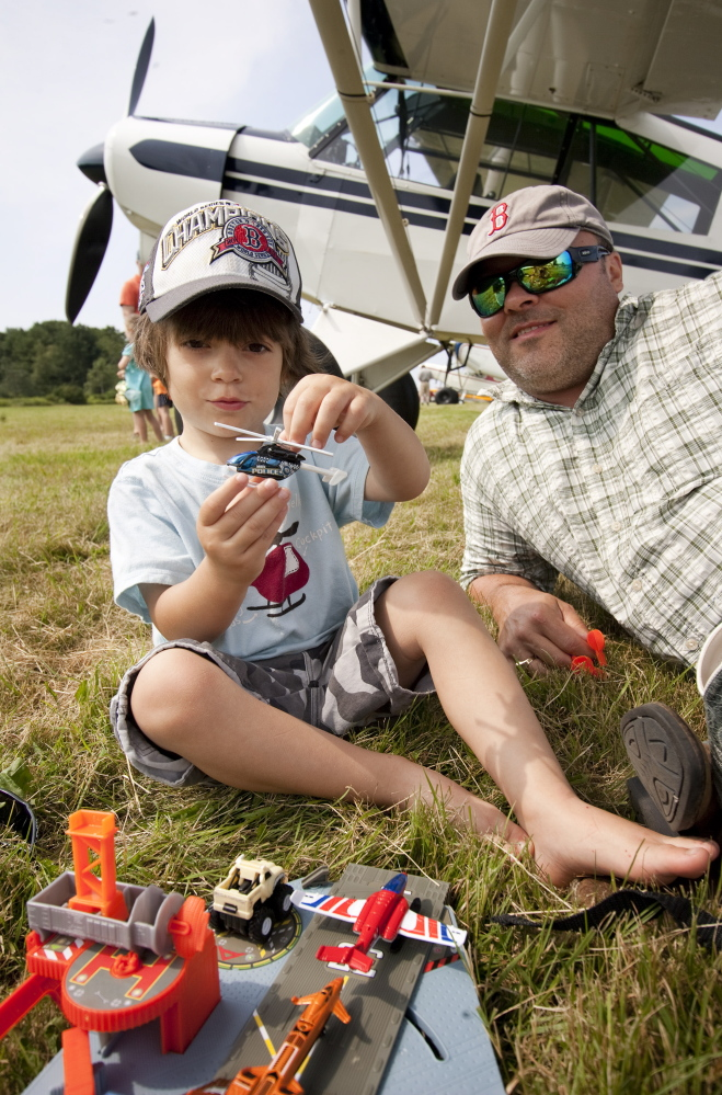 Jed Bucci, 3, of Cape Elizabeth, plays with a toy Sunday while sitting with his father, Jeff Bucci, near the family plane during the fly-in at Sprague Field in Cape Elizabeth.