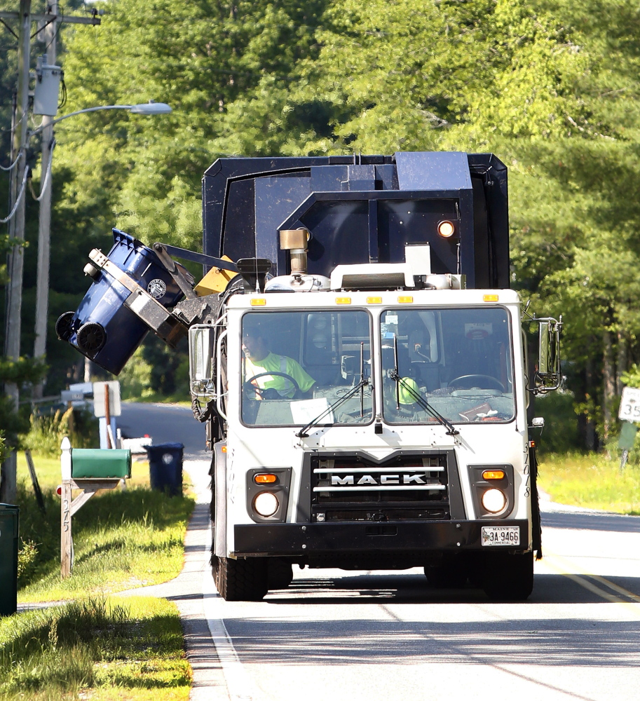 A Pine Tree Waste Services recycling truck empties a container Tuesday in Biddeford. The city of Biddeford has completed its first year of curbside recycling and saved more than $200,000 in trash disposal fees.