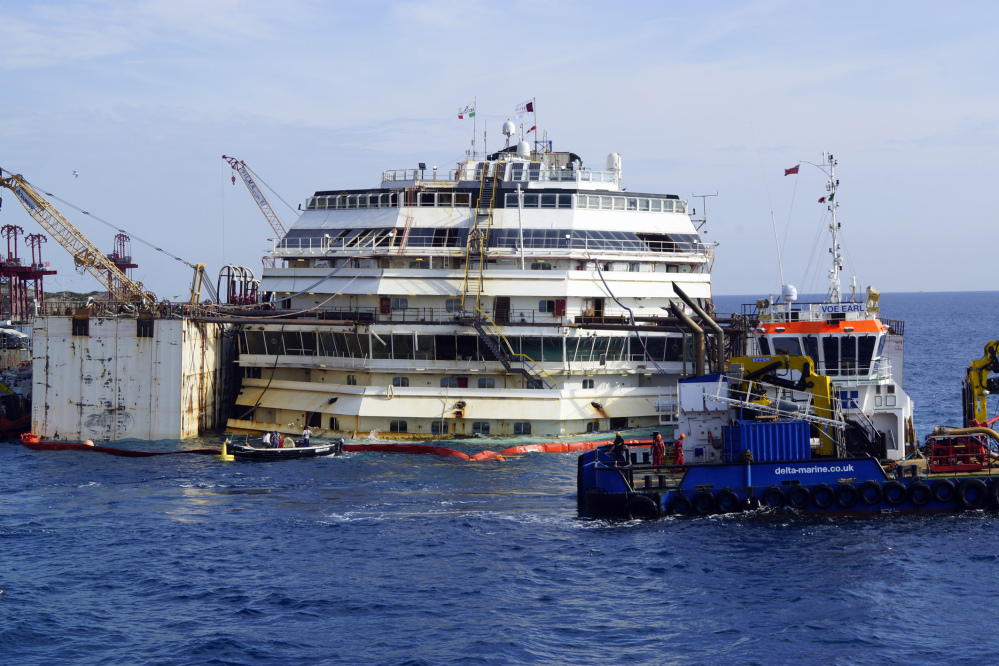 Workers carry on the operations on the luxury cruise ship Costa Concordia, to put put it afloat, on the tiny Tuscan island of Giglio, Italy on Monday. The shipwrecked Costa Concordia has been successfully put afloat in preparation to tow it away for scrapping.