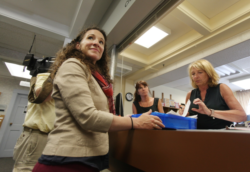 Melissa Thomas, left, turns in signed petitions to South Portland Assistant Clerk Karen Morrill, right, and Alice Kelley, center, on Monday at South Portland City Hall in South Portland. The petitions are in support of an initiative to make marijuana possession legal for adults in city limits.