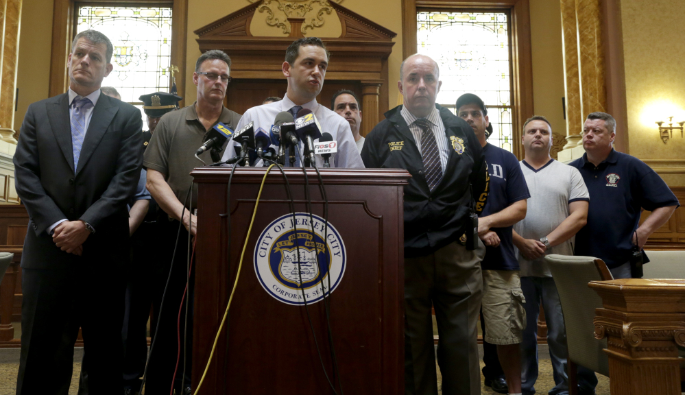 Jersey City Mayor Steven Fulop, center, addresses the media during a news conference talking about an early morning shooting which lead to a suspect and a Jersey City Police Department officer killed, Sunday, in Jersey City, N.J.