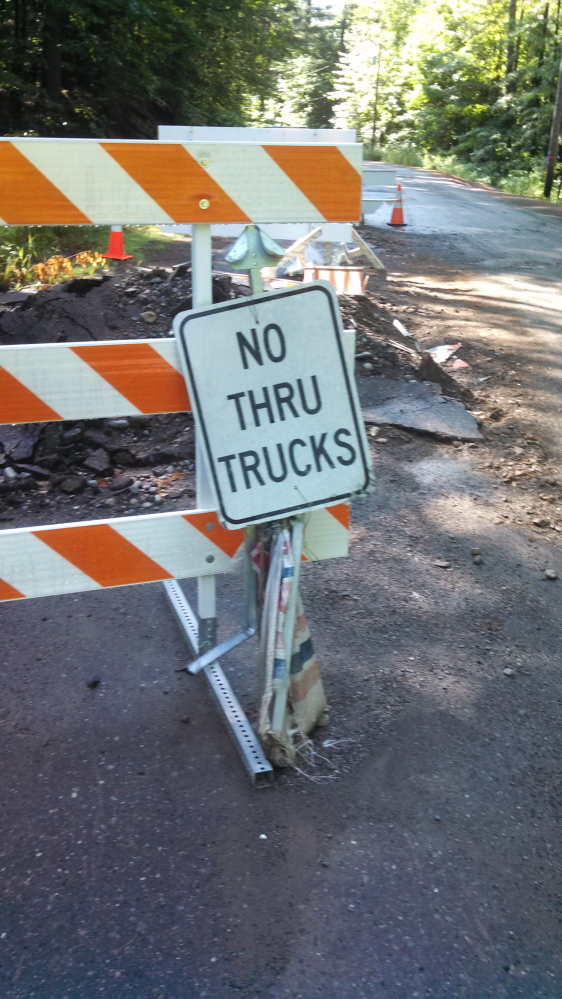 A sign warning trucks not to head down a closed dirt road have been vandalized in Phillips.