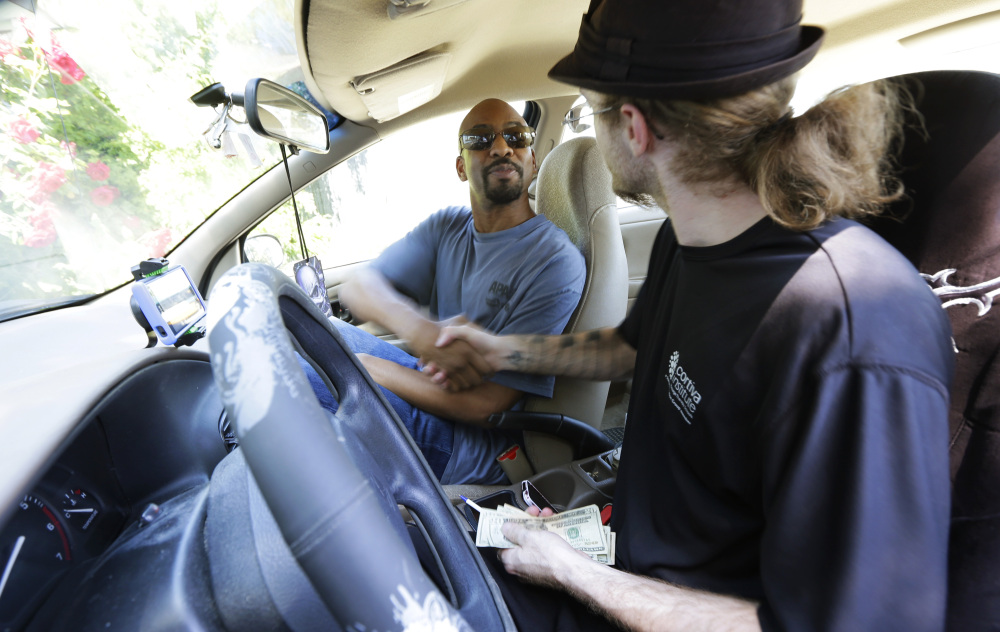 """Michael """"Billy the Kid"""" Kenworthy, right, a marijuana delivery driver, greets a customer who identified himself as """"Mr. Jones"""" after conducting a transaction in Kenworthy's car. Kenworthy works for Winterlife, a pot delivery service in Seattle."""