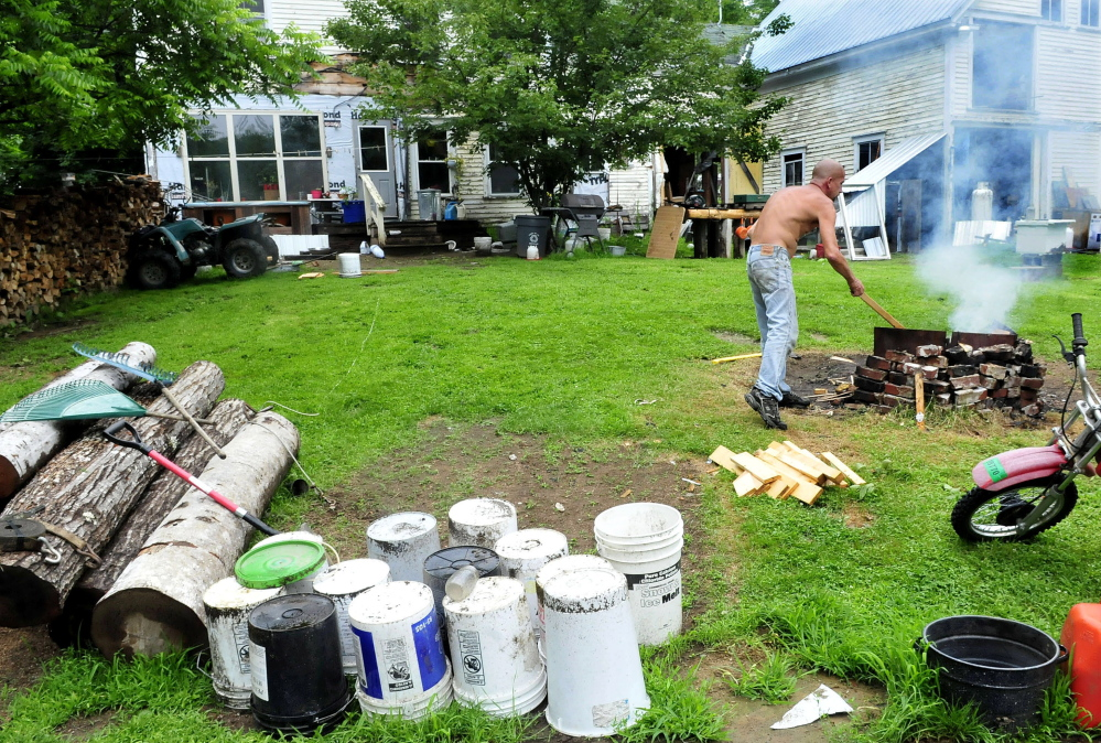 Duane Pollis stokes an outdoor fire pit with wood in the front yard of his home in Wilton on Wednesday. Pollis has removed a considerable amount of items in his yard that put it in violation of a town ordinance. Town officials said this week they are pleased with the progress of the cleanup.
