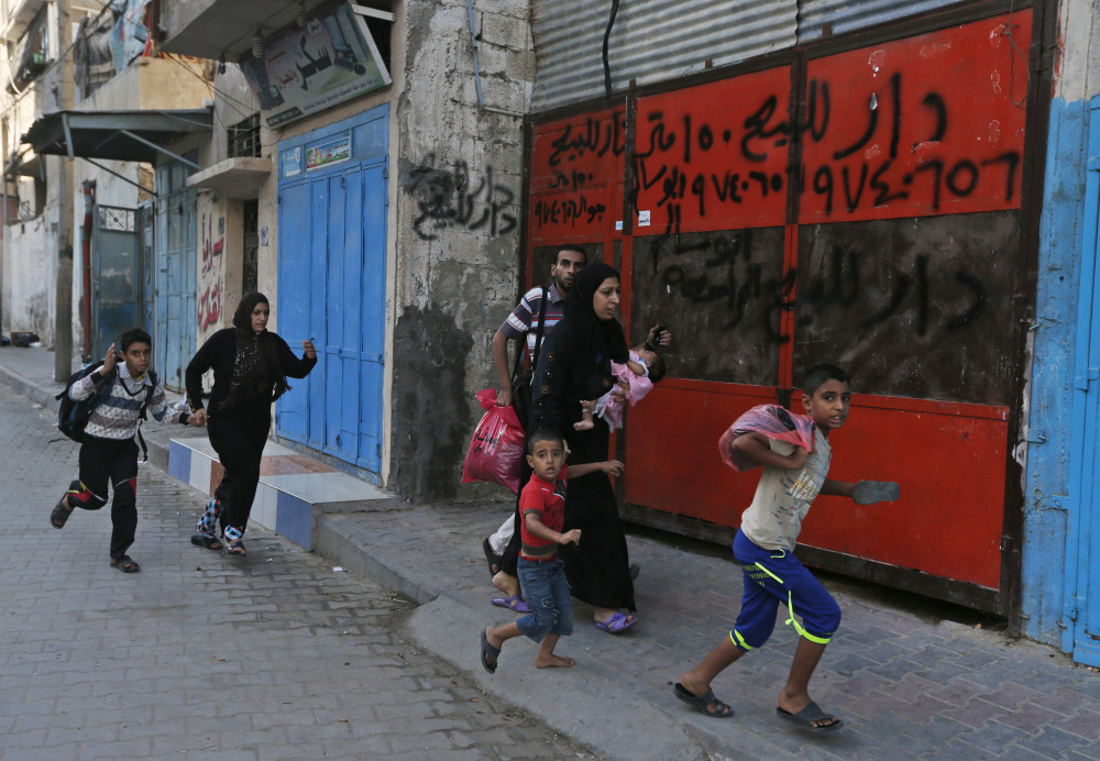 Palestinians run for shelter as they hear bombing in the distance while they flee their homes in the Shajaiyeh neighborhood of Gaza City, after Israel had airdropped leaflets warning people to leave the area, on Wednesday.