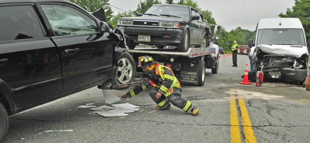 A firefighter puts down pads to absorb fluid leaking from a wrecked car as tow truck drivers clear U.S. Route 202 after a collision at the intersection of Route 202, Bog Road and Blue Road on Wednesday in Monmouth.