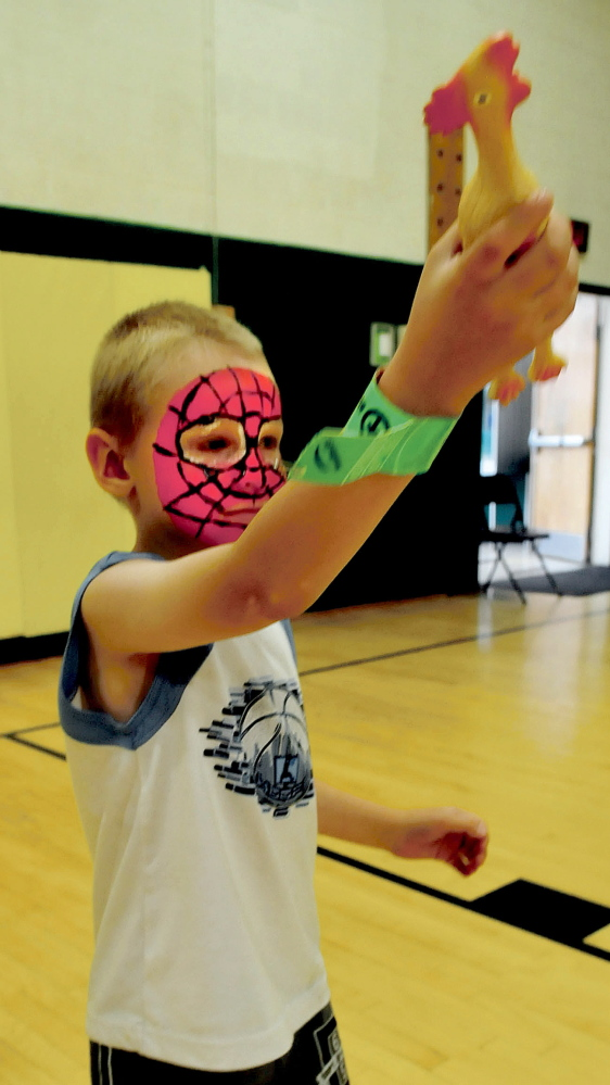After getting his face painted Patrick Hyde takes aim with a rubber chicken before throwing it in distance competition during the Eggolympics held at the Warsaw School in Pittsfield on Wednesday. More events occur daily with a big parade scheduled for Saturday morning.