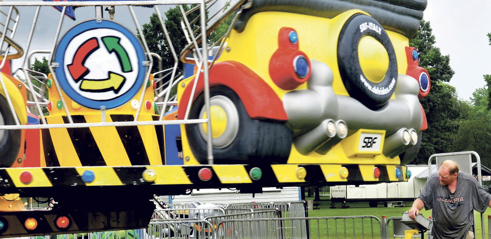 Carnival worker Chris Verrill looks under a rotating ride during an inspection in Manson Park in Pittsfield on Wednesday. The carnival, part of this years Central Maine Egg Festival, opens Thursday  at 6 pm.