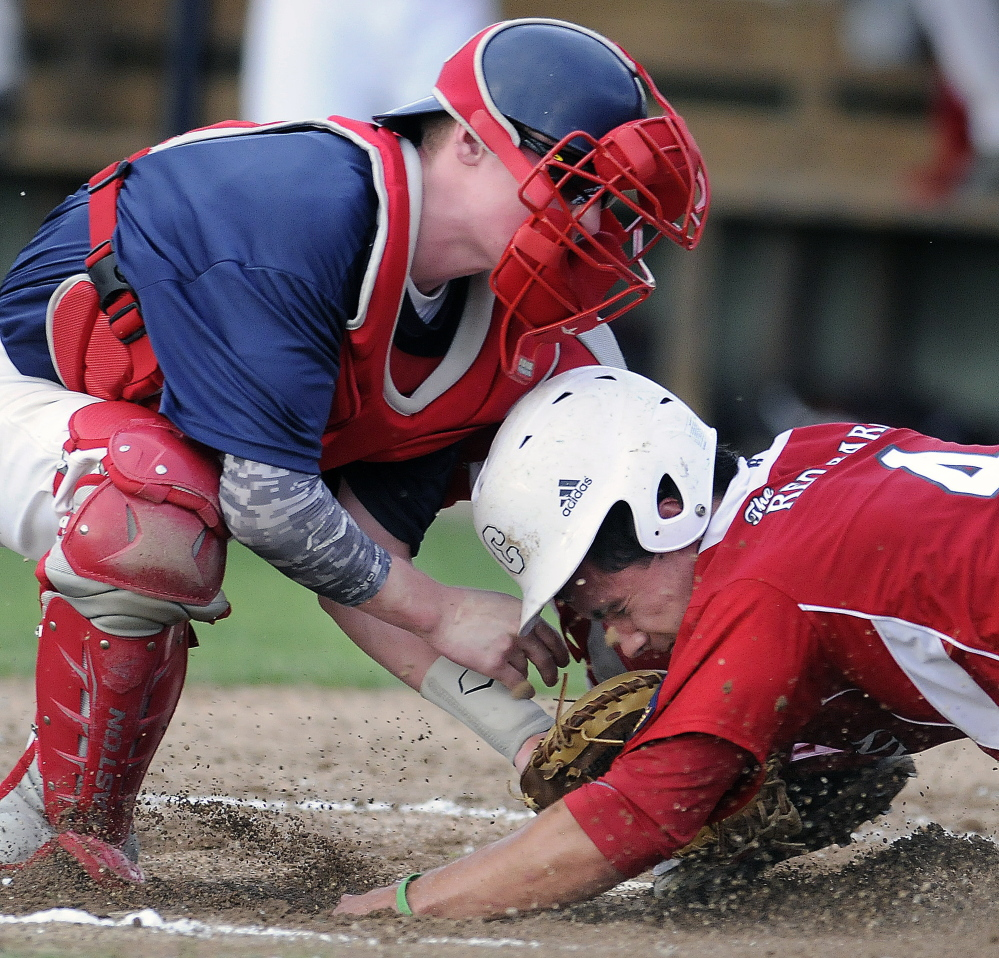 Post 51's Trevor Gettig tags Red Barn's Taylor Carrier at home during an American Legion playoff game in Augusta. Post 51 beat The Red Barn 4-0.