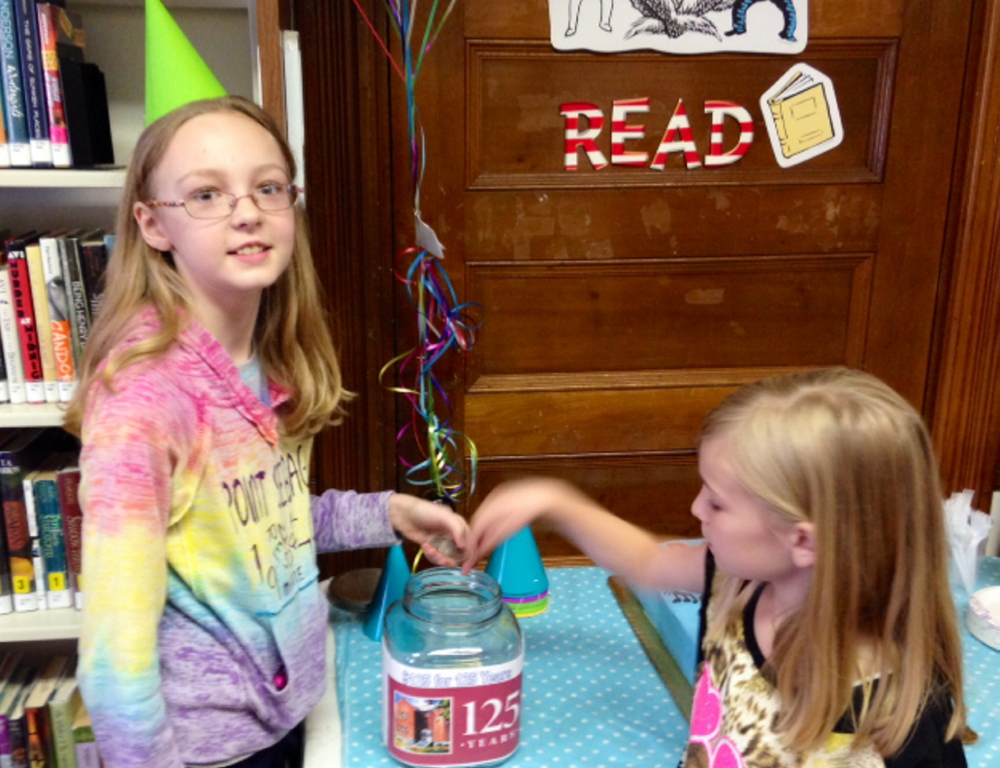 Gracie Demchak, 12, and her sister Maggie, 9, add their money to the Skowhegan Library's $125 for 125 Years Jar at a party held recently to celebrate the Skowhegan Free Public Library's 125th birthday. The $125 goal was reached during the party, the money will benefit the library's renovation.