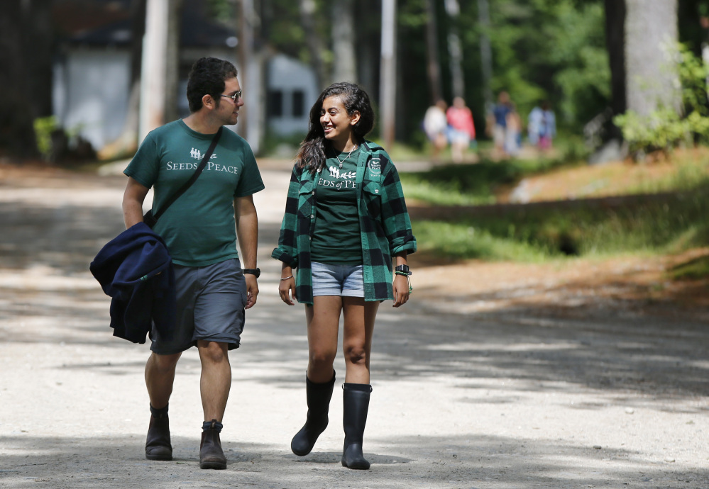 Camp counselors Hagai Dfrat, 23, of Israel, left, and Monica Baky of Egypt talk while walking on the grounds of the Seeds of Peace camp in Otisfield.