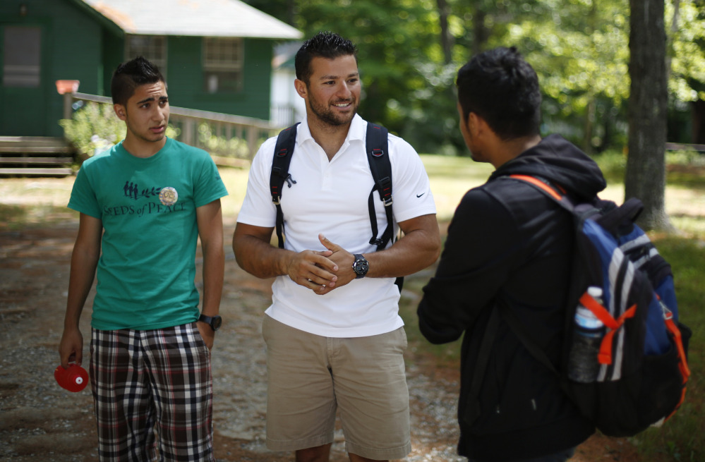 Seeds of Peace camp counselor Eias Khatib, 25, of Palestine, center, talks with a camper in Otisfield this week.