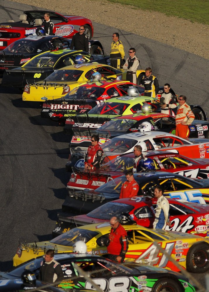 Drivers stand by their vehicles before the start of the National Anthem at the 40th Annual TD Bank 250 at Oxford Plains Speedway July 21, 2013. This year's race is Sunday.