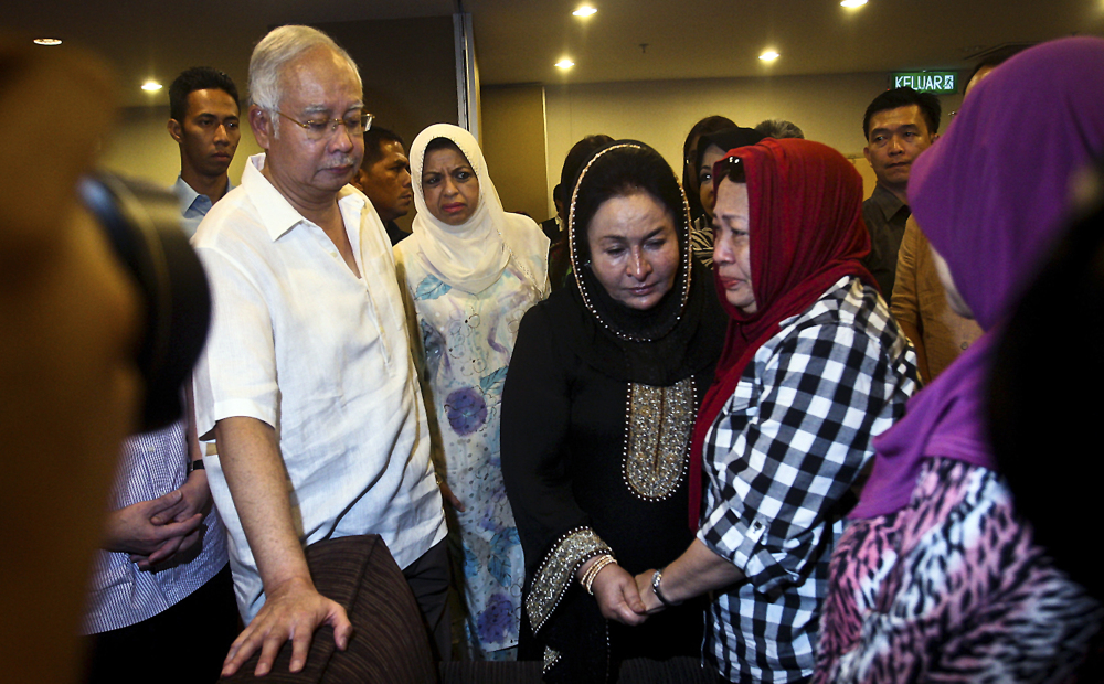 "Malaysian Prime Minister Najib Razak, left, and his wife Rosmah Mansor, center in black, meet family members of the passengers on board Malaysia Airlines MH 17, at a hotel in Putrajaya, Malaysia, on Saturday. Malaysia's transport minister said the country is ""deeply concerned"" that the site in Ukraine where the Malaysia Airlines jetliner was shot down with 298 people onboard ""has not been properly secured."""
