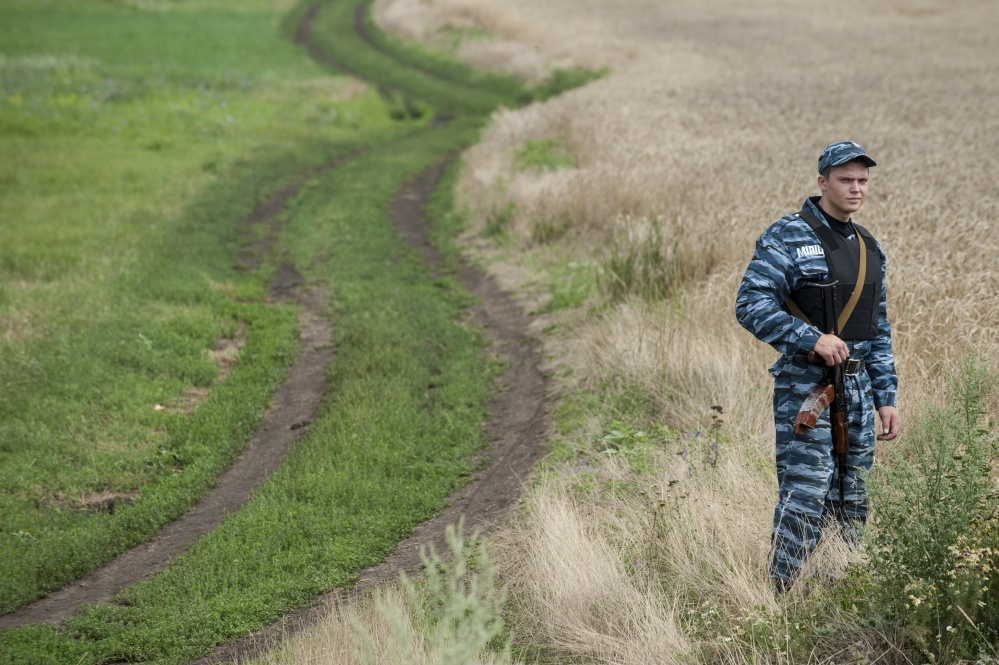 A pro-Russian fighter stands in a field at the crash site of a Malaysia Airlines jet near the village of Hrabove, eastern Ukraine, on Saturday.