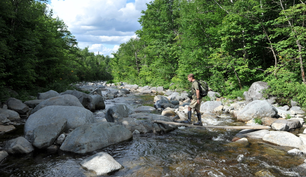 Peter Hinman, 56, of Toronto, crosses the Carrabassett River while hiking a section of the Appalachian Trail near Wyman Township on Wednesday.