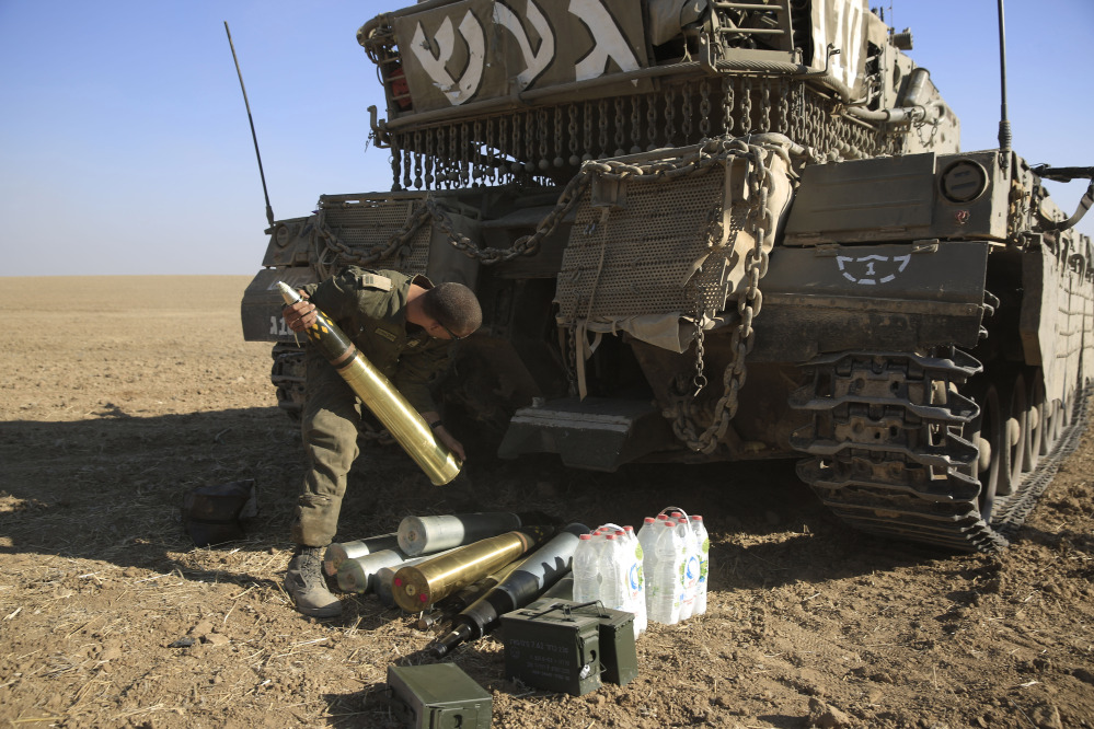 An Israeli soldier loads tank shells near the border of Israel and the Gaza Strip on Sunday. Escalating their ground offensive, Israeli troops backed by tanks and warplanes battled Hamas militants in a crowded neighborhood of Gaza City early Sunday.