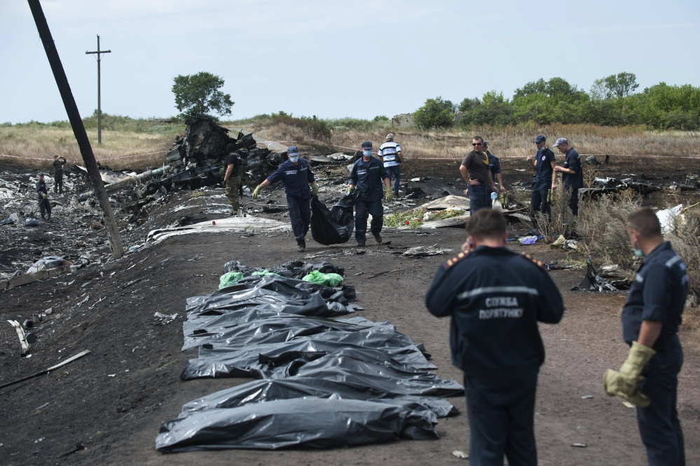 Ukrainian Emergency workers carry a victim's body in a bag as pro-Russian fighters stand in guard at the crash site of Malaysia Airlines Flight 17 near the village of Hrabove, eastern Ukraine, Sunday.