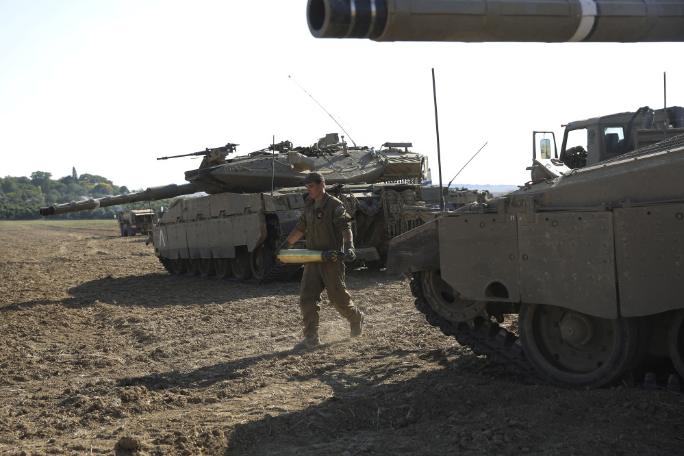 An Israeli soldier carries a tank shell near the border of Israel and the Gaza Strip, Sunday.