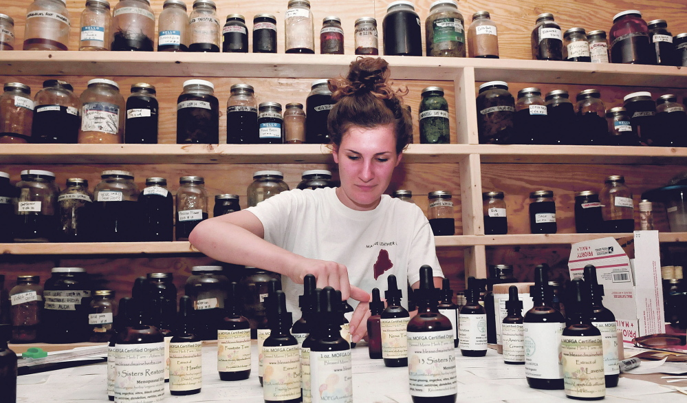 Belle Hilmer creates tinctures on Thursday made with ingredients grown at Blessed Maine Herb farm in Athens.