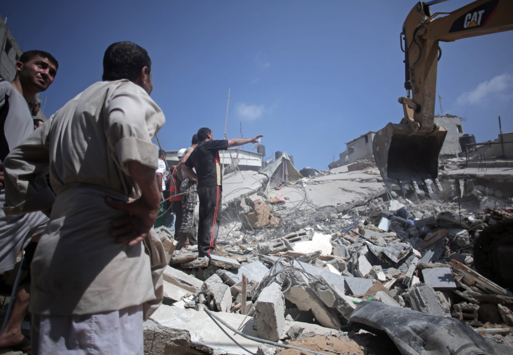 Palestinian rescuers search for bodies and survivors in the rubble of homes that were destroyed by an Israeli missile strike, in Gaza City on Monday.