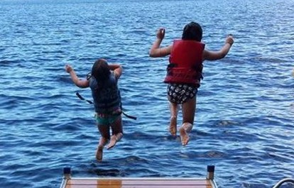 Photo courtesy of Allicia Rogers Golden   Emerson, left, and Charlie Golden, of Solon, jump off the dock at their family's camp on Embden Lake recently.