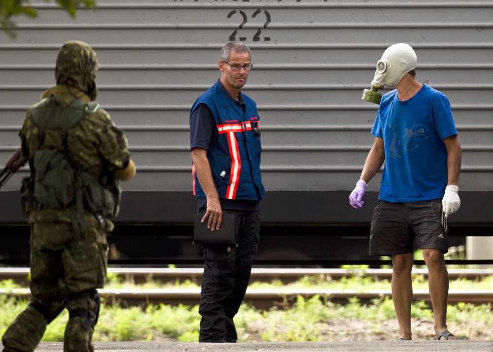 Peter Van Vilet, center, team leader of Holland's National Forensic Investigations Team, stands on the platform after observing the loading of newly retrieved bodies of passengers on a refrigerated train in Torez, eastern Ukraine, 9 miles from  the crash site of Malaysia Airlines Flight 17, on Monday.