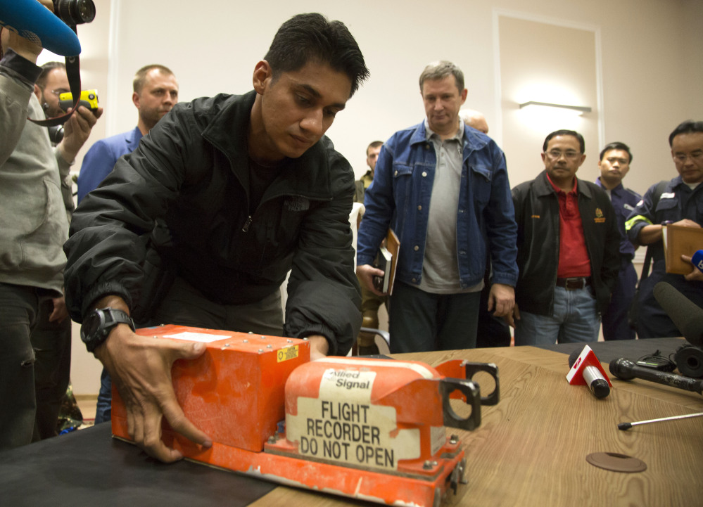 A Malaysian investigator takes a black box from Malaysia Airlines Flight 17 as it is handed over from Donetsk People's Republic officials to Malaysian representatives in the city of Donetsk, eastern Ukraine Tuesday.