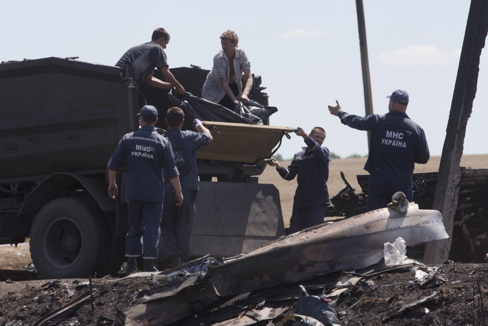 Forensic experts load remains of victims of the Malaysian Airlines plane crash at Hrabove, Donetsk region, eastern Ukraine, on Monday. Outrage over the delays and the possible tampering of evidence at the site was building worldwide.
