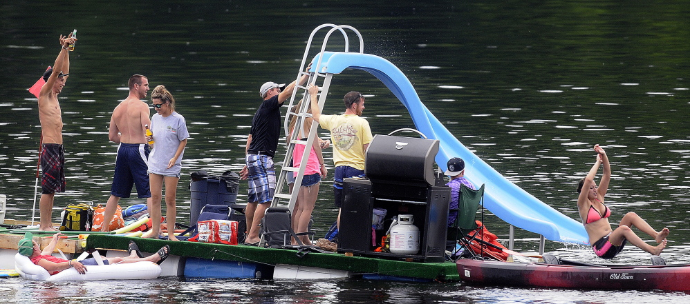 A raft on barrels carrying a water slide and a grill meanders down the Kennebec River on Sunday between Hallowell and Chelsea. More than 200 people showed up with inflated rafts, launched kayaks and drifted atop empty coolers during the second annual celebration of the river, which launched from Chelsea and Hallowell and came aground in Gardiner.