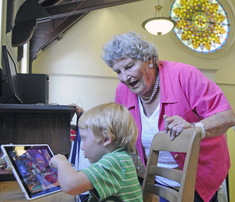 Randolph resident Shirley Hanley chats with Bimas Brown on Monday while he plays a game in the children's reading room at the Gardiner Public Library. Hanley, who has been member of the library for 70 years, was selecting titles for her grandchildren.