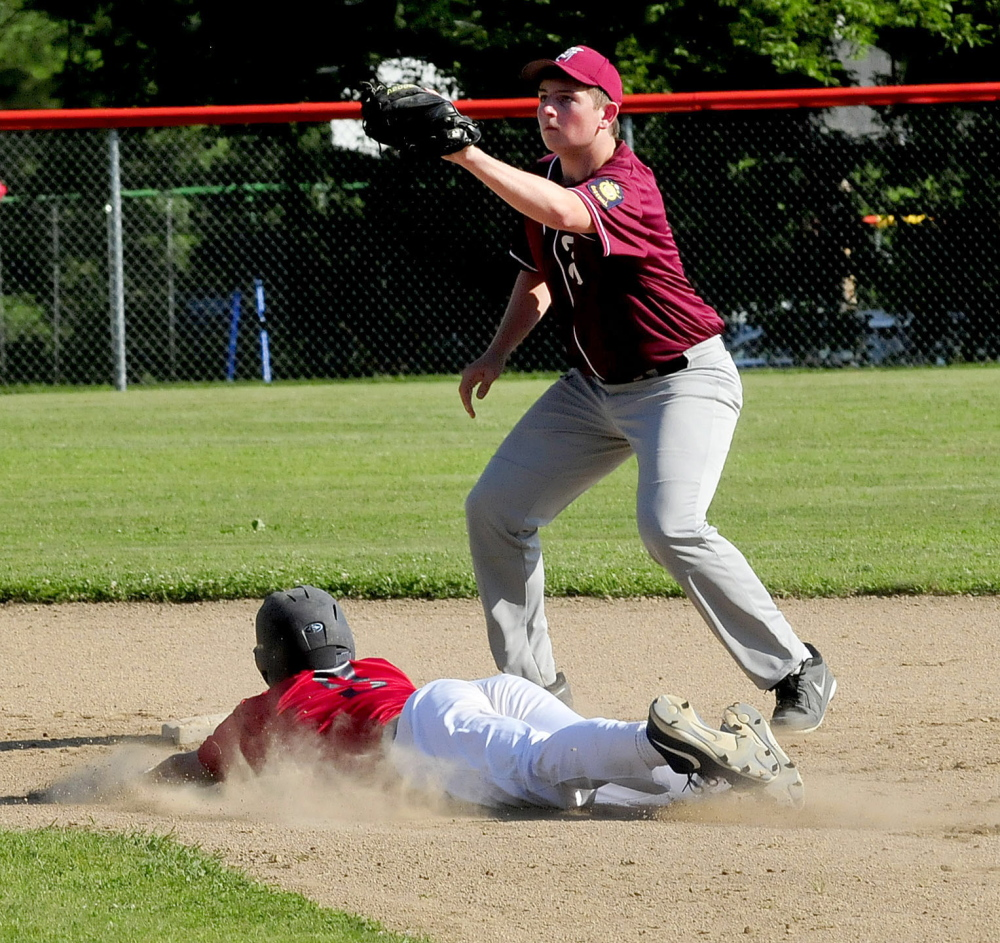 Post 51 runner Zach Mathieu slides safely into second base as Franklin County Flyers' Sebastian Lombardi waits for throw Monday in Skowhegan. Post 51 won 10-0.